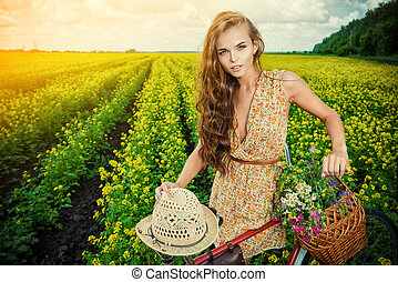 bicycle romance - Romantic young woman stands in a field...