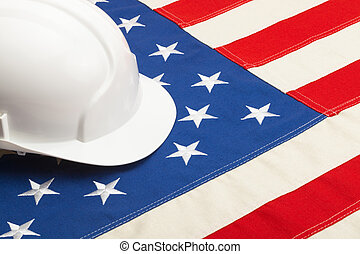 White color construction helmet laying over USA flag -...