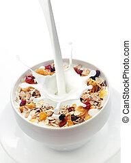 Milk splashing into a bowl of fresh muesli with a mix of...
