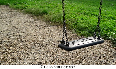 Empty swing seat swaying at playground in the park....