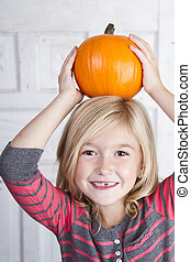 child holding small pumpkin on her head - Cute child holding...