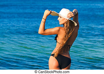 beautiful young woman with long hair in a straw hat sea in...