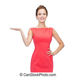 smiling woman holding something imaginary on palm -...