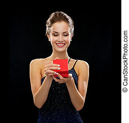 smiling woman holding red gift box - holidays, presents,...