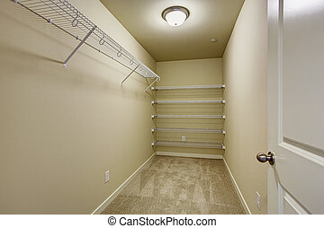 Empty walk-in closet - Empty narrow walk-in closet with...