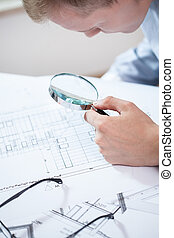 Engineer analyzing the plan - Young engineer analyzing the...