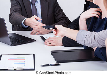 Female hand giving manager phone on business meeting