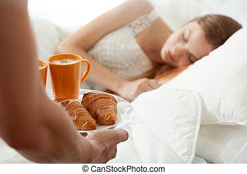 Surprise breakfast for sleeping woman
