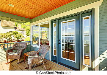 Walkout deck with wicker chairs.
