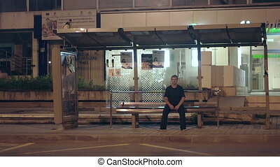 at the station - a man sitting alone at night in a bus...