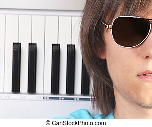 Portrait of young man in sunglasses with piano