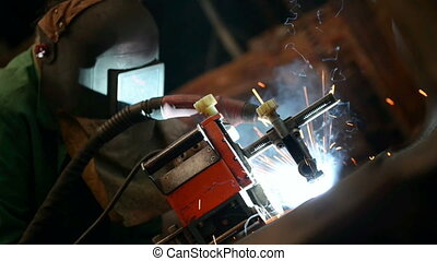 Welder working in factory with welder machine