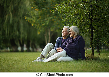 Nice mature couple - Nice mature couple sitting on green...