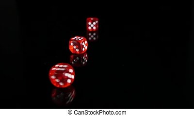 Throwing red dice on a black background. 3 pack. Slow motion.