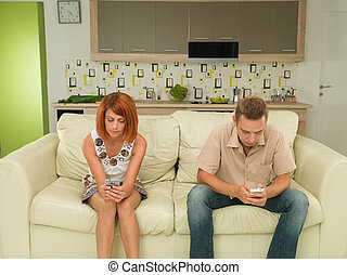 couple texting to each other - young caucasian man and woman...