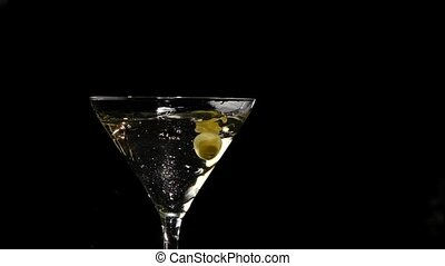 One olive falls into martini glass Slow motion
