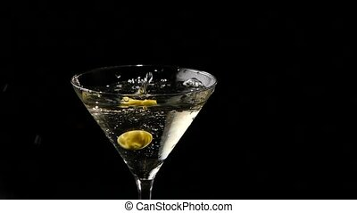 Two olives falling into a glass of martini Slow motion
