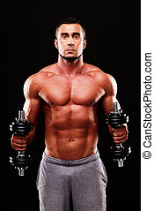 Handsome sexy sportsman working out with dumbbells over...