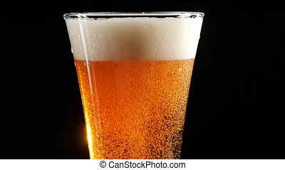Beer is pouring into a glass on black background. Slow motion.
