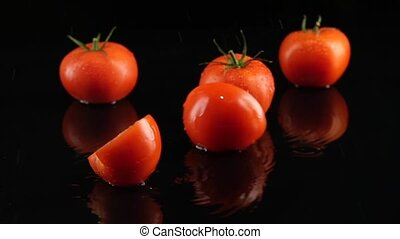 Tomatoes are falling on the table black background. Slow motion.