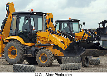 Big Diggers - Two JCB 3CX diggers on a dusty site with a...