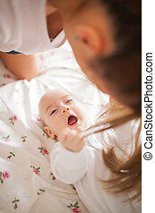 Naughty baby boy pulling mother's hair with his hands