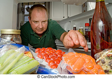 Man in Refrigerator - A man selecting various items from a...
