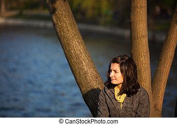 Nostalgic woman near lake - Young nostalgic woman is sitting...