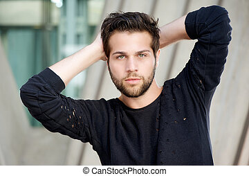 Male fashion model posing with hands behind head