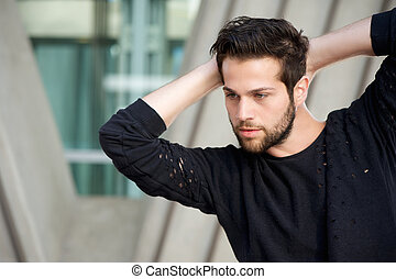 Handsome male fashion model posing with hands behind head