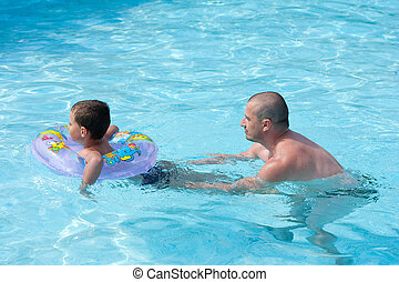 Swimming lesson - Father teaching his son how to swim, in a...