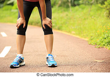 tired woman runner taking a rest after running hard in...