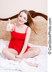 portrait of showing thumb up beautiful woman blue eyes girl sitting on white bed in a red dress laughing happy smiling & looking at the camera picture