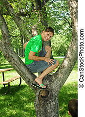 in the tree - happy caucasian young woman sitting in a tree