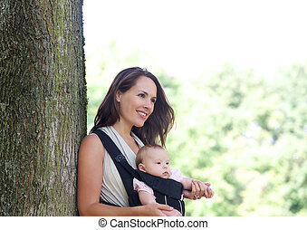Mother smiling with infant in baby carrier - Portrait of a...