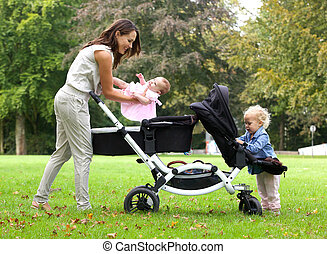 Mother and daughters with pram outdoors - Portrait of a...