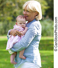 Grandmother smiling with baby granddaughter