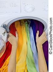 woman taking color clothes from washing machine - woman...