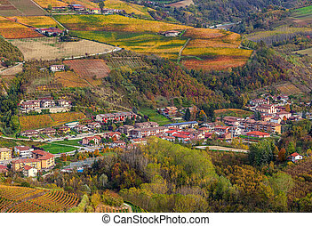 Small town among autumnal hills in Italy. - Small town among...