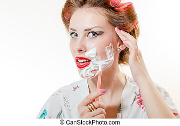 Beautiful young pinup woman shaving face looking in camera...