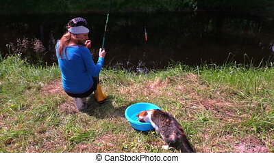 pregnant woman fish cat - Woman fishing on lake shore and...