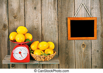Lemons on scales and in a basket on a wooden shelf A...