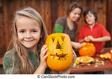 Little girl showing her Halloween jack-o-lantern - Little...