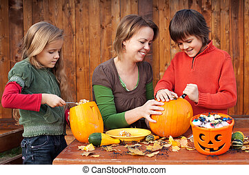 Woman helping kids to carve their Halloween jack-o-lantern -...