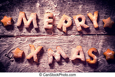 Merry Xmas text with cookies in the wooden background from...