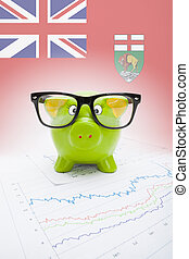 Piggy bank with Canadian province flag on background -...