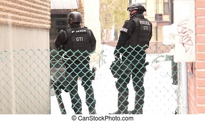 SWAT police hiding between building - Two SWAT officers...
