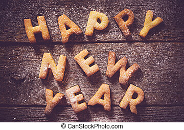 Happy New Year text with cookies on the wooden background...