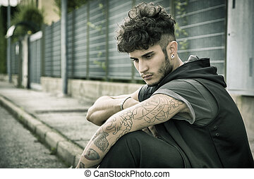 Young man in city sitting on pavement - Attractive...