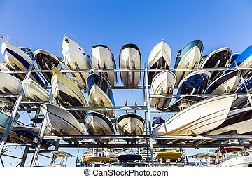 speed motor boats are stapled in a garage system in the...